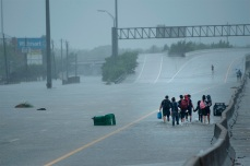 TOPSHOT - Evacuation residents from the Meyerland area walk onto an I-610 overpass for further help during the aftermath of Hurricane Harvey August 27, 2017 in Houston, Texas. Hurricane Harvey left a trail of devastation Saturday after the most powerful storm to hit the US mainland in over a decade slammed into Texas, destroying homes, severing power supplies and forcing tens of thousands of residents to flee. / AFP PHOTO / Brendan Smialowski (Photo credit should read BRENDAN SMIALOWSKI/AFP/Getty Images)