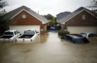 Houses and vehicles at the Highland Glen subdivision stand in floodwaters due to Hurricane Harvey in Spring, Texas, U.S., on Monday, Aug. 28, 2017. A deluge of rain and rising floodwaters leftHoustonimmersed and helpless,crippling a global center of the oil industry and testing the economic resiliency of a state that's home to almost 1 in 12 U.S. workers. Photographer: Luke Sharrett/Bloomberg via Getty Images
